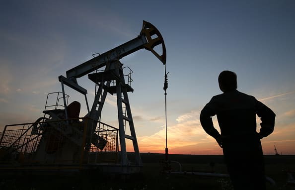 The sun sets beyond an oil pumping unit, also known as a 'nodding donkey' or pumping jack.
